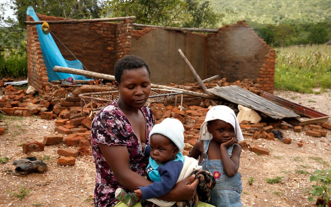 Woman and children in front of home destroyed by Cyclione Idai in Zimbabwe
