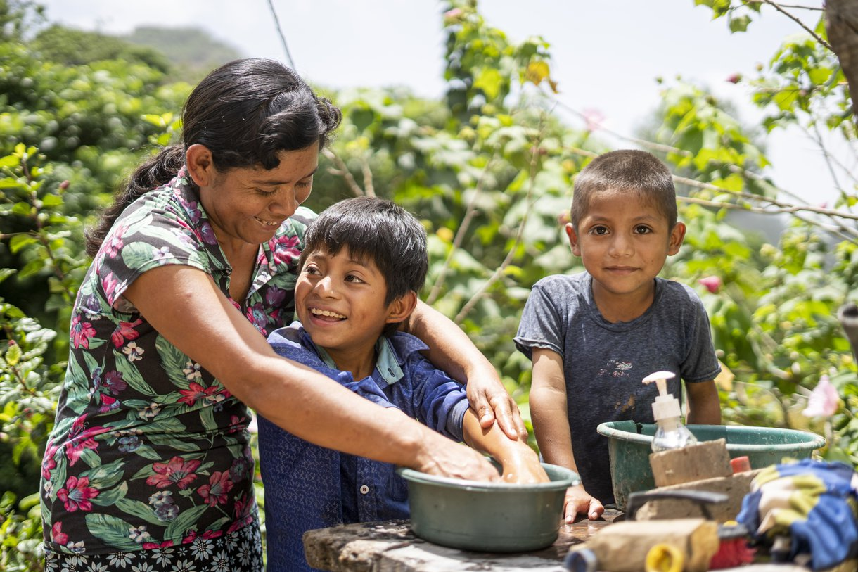 Juana Gutiérrez washes her son's hands at their home in Guatemala, in part of the country known as the Dry Corridor. Oxfam has been helping families here with soap to ensure they do not get water-borne diseases.
