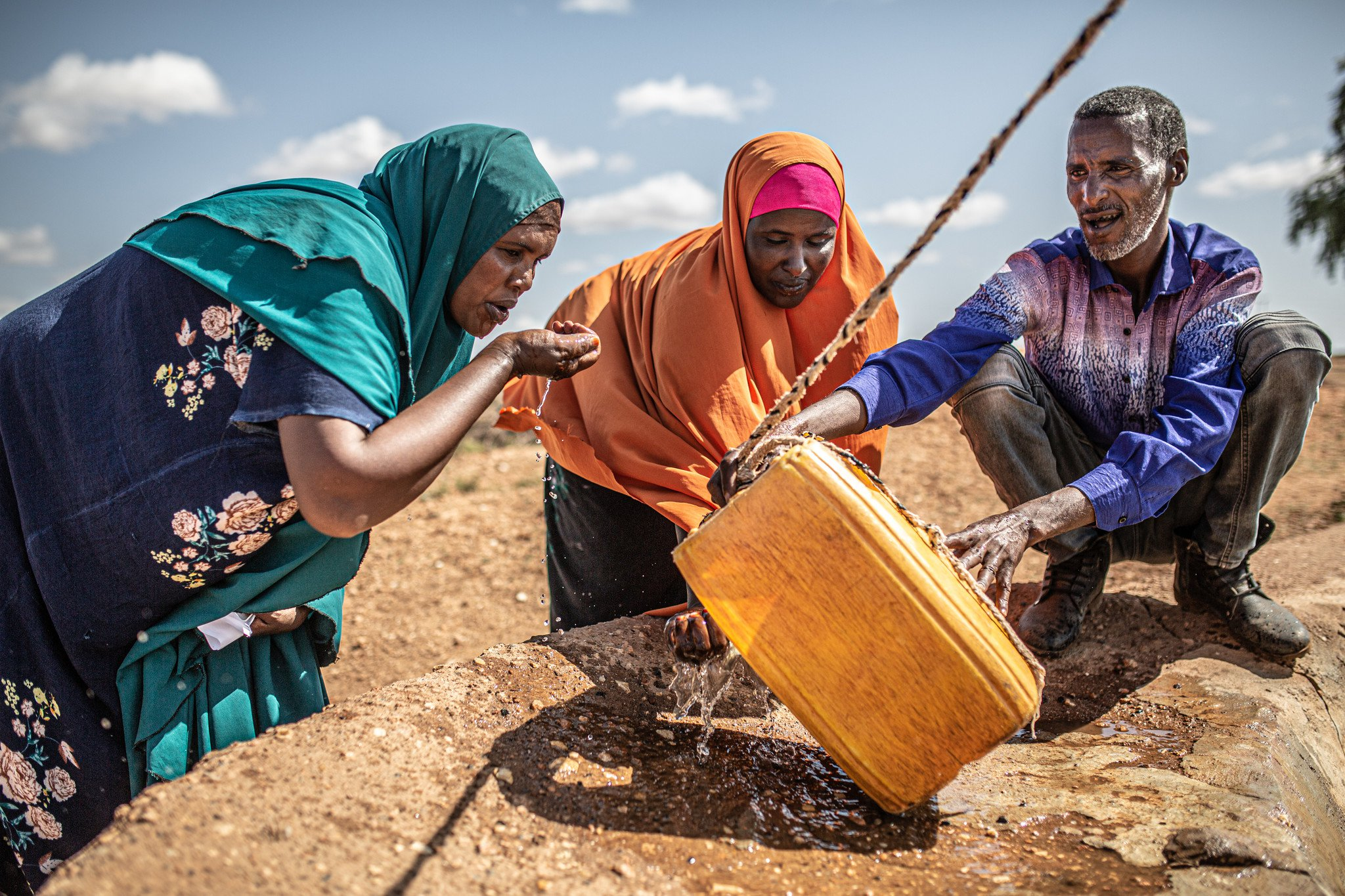 Hoden Abdi Iwal (left) and her neighbors get water from a reservoir near her home.