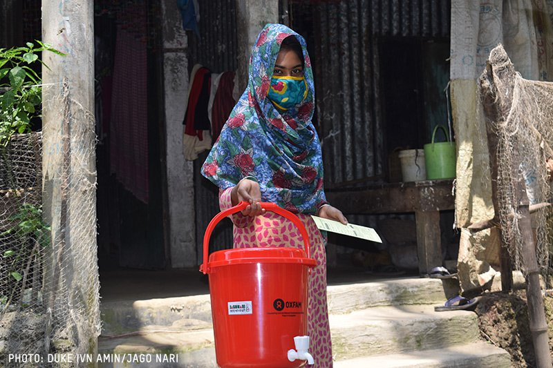 A woman carrying a bucket of water