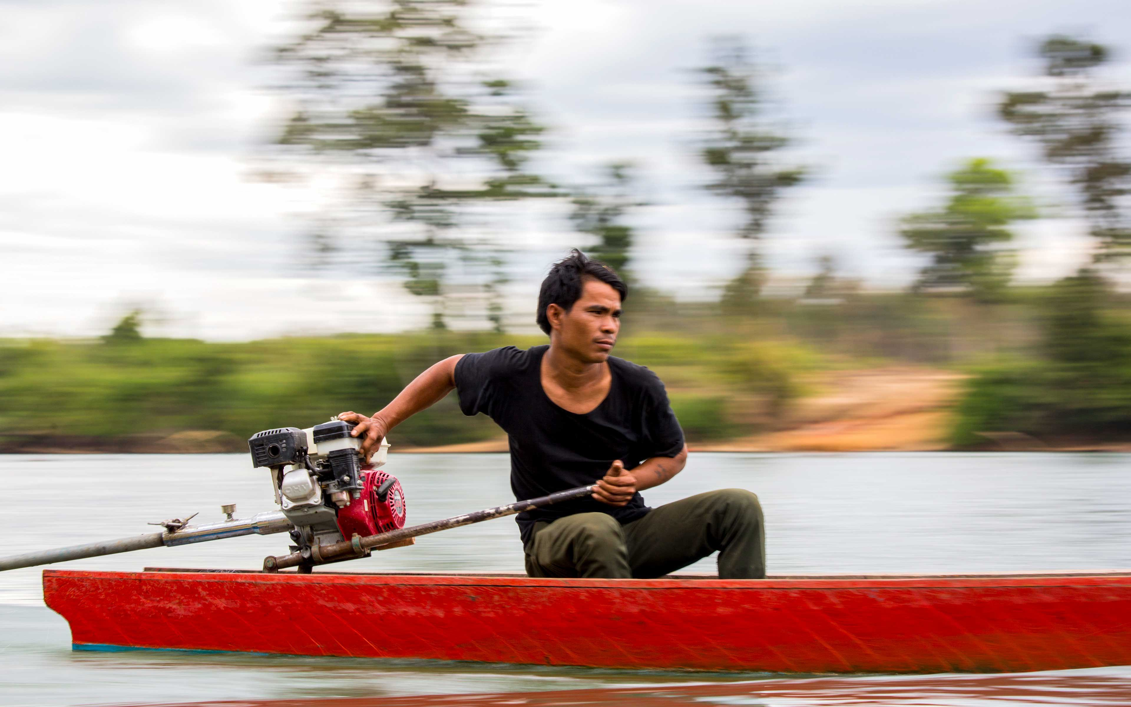 """Romas Shyob pilots his boat on the Sesan near his village, Padol. He says the participation of women in protecting the forest and guiding the community is essential. """"When there is an opportunity to send people to represent the community, we send women,"""" he says."""