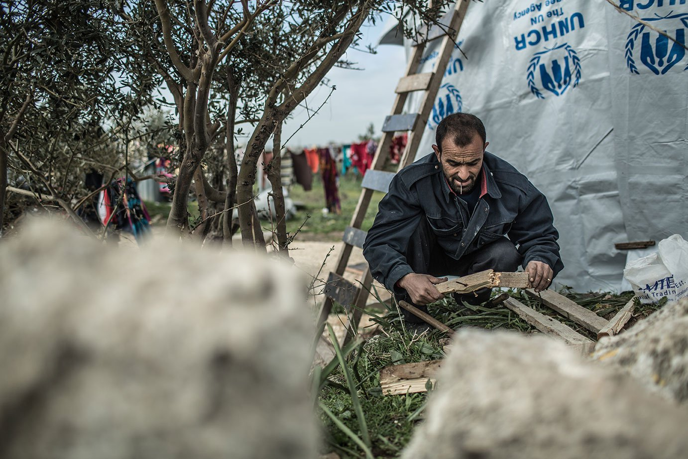 A Syrian man builds a shelter out of tarps and other material in Lebanon. Fighting has forced millions of Syrians to flee their country.