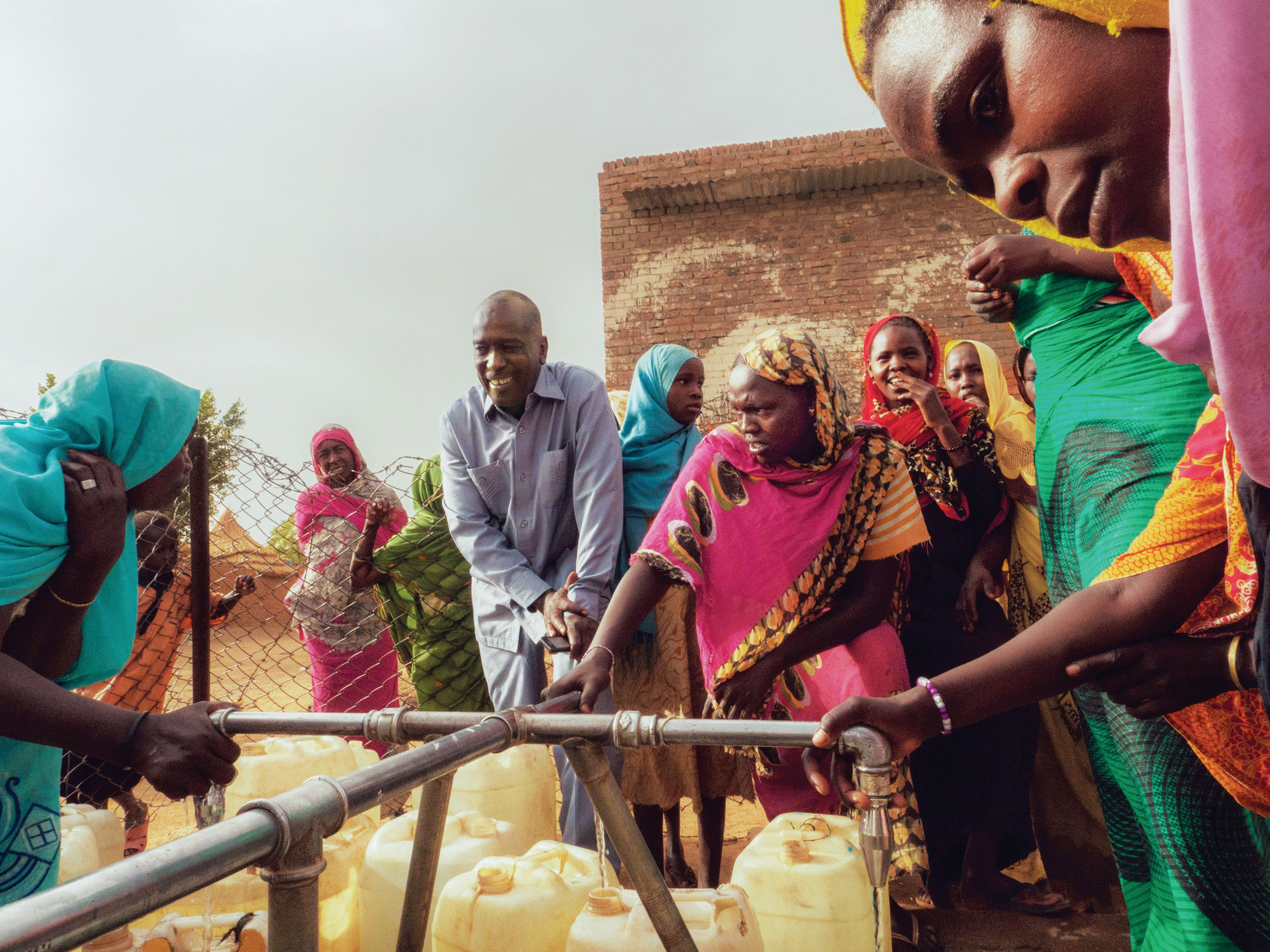 """Mohammed Mohammedian of KSCS chats with women collecting water at a tap stand in Kebkabiya. """"In the past five years, there have been four major crises in the area of Kebkabiya. In each case, we were the first aid agency to arrive with help."""""""