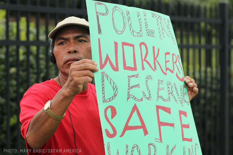 A poultry worker holding a protest sign