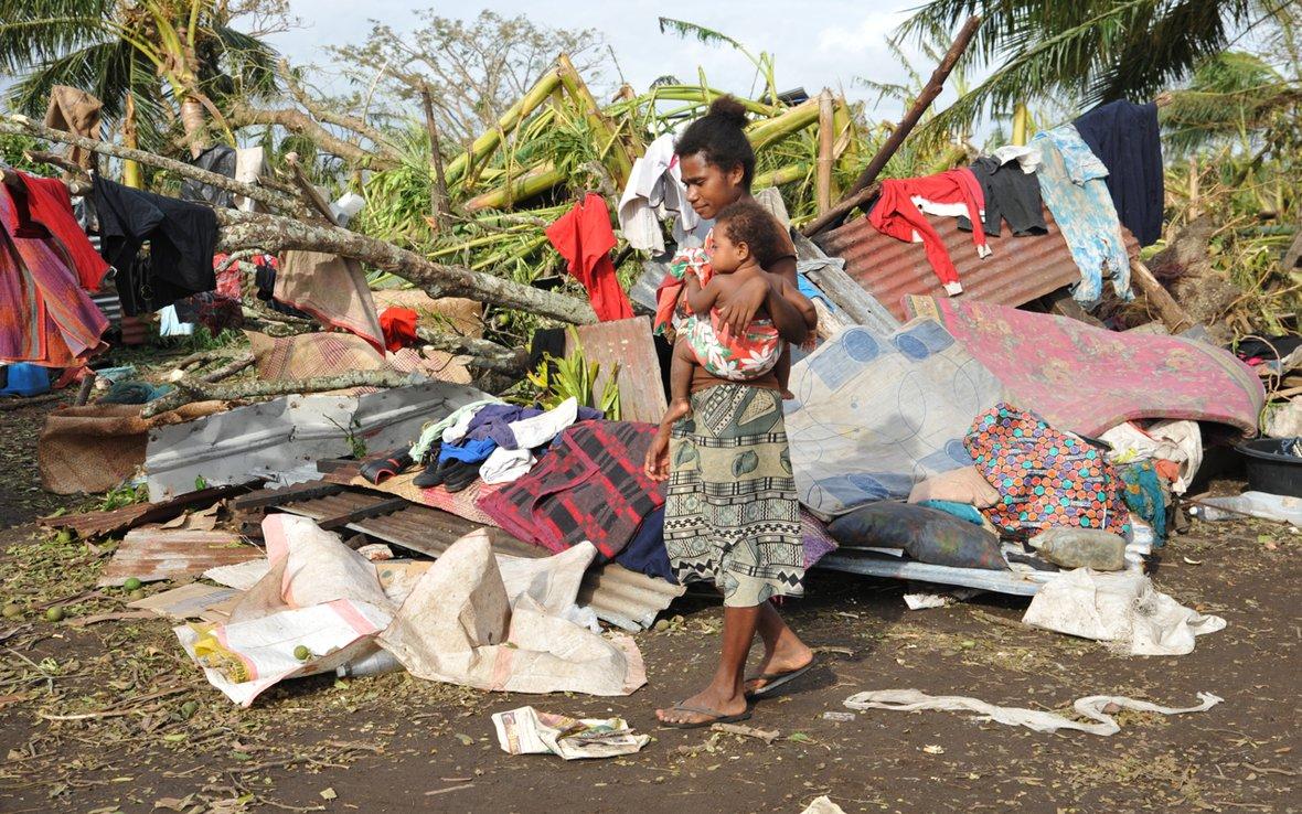 Woam carrying child through wreckage 78504.jpg