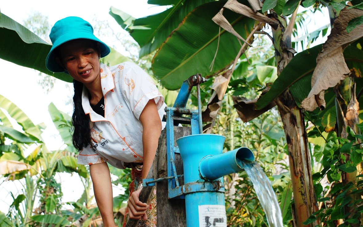 Yem Neang pumps water from well to water the plants in her garden