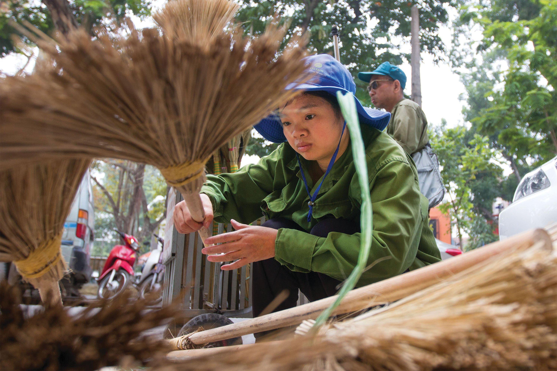 Pham Thi Hâu and her uncle, Phùng Bá Nghĩa, walk the streets of Hanoi, Vietnam, selling brooms.