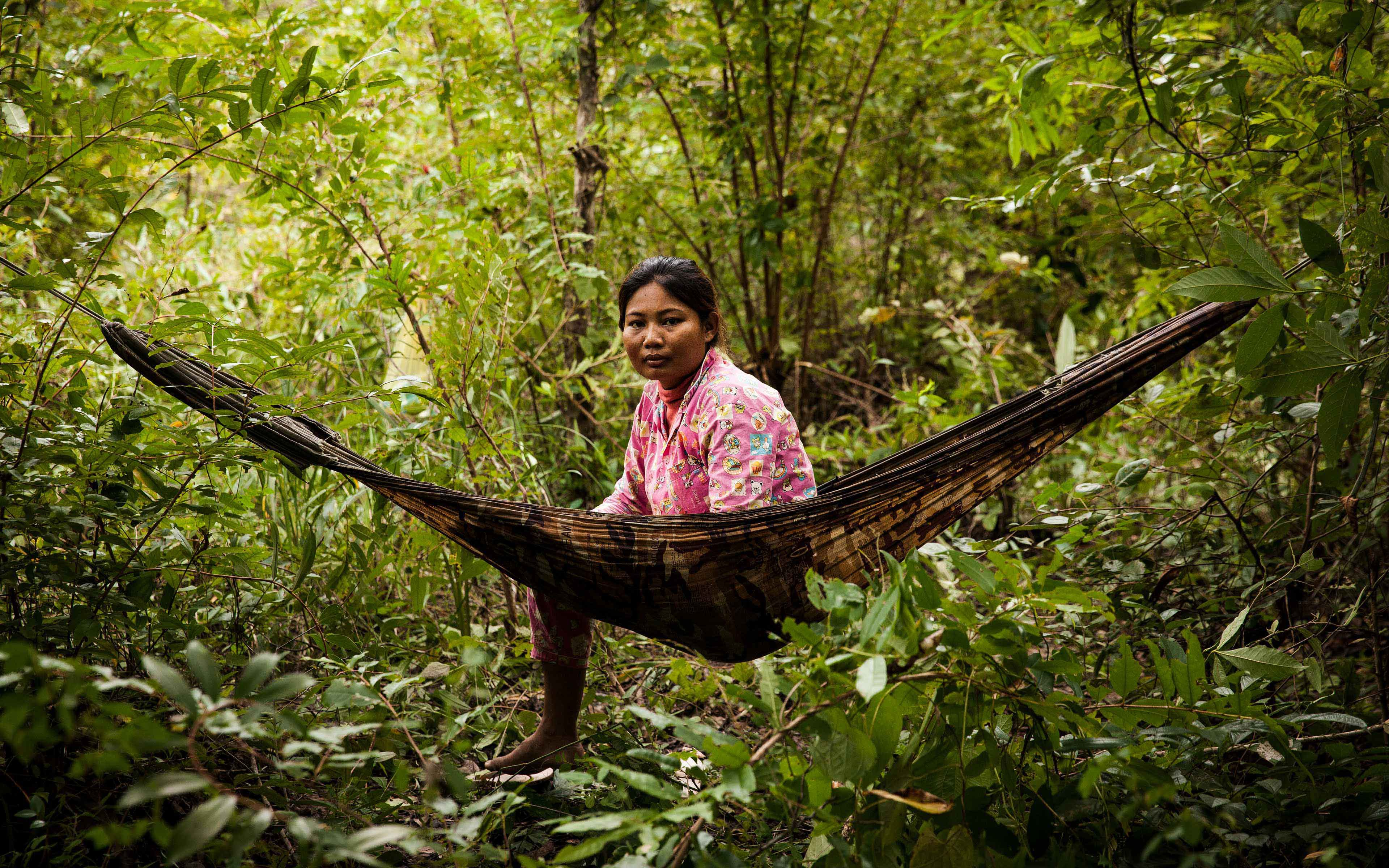 """Phorn Sopheak, 26, was sleeping in this hammock deep in the Prey Lang protected forest when someone attacked her and badly injured her foot. """"The government has laws to protect the forest,"""" she says, """"but I don't see a lot of enforcement of the laws, and I see a lot of people taking wood out of the forest … people are cutting down the trees."""""""