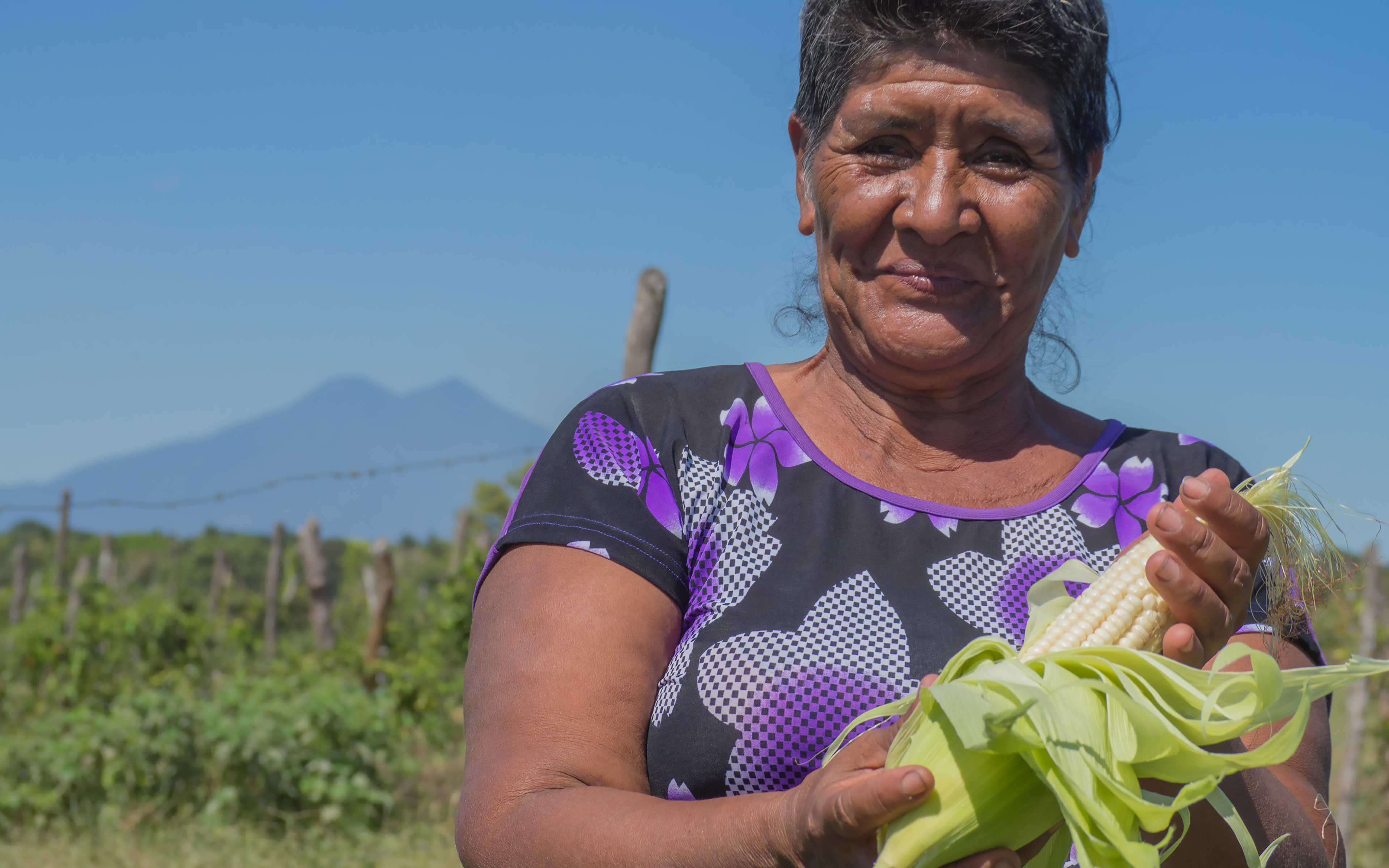Flor Aquino displays corn grown on a community plot in El Ranchón. While the country is reeling from the effects of El Niño, corn and beans are thriving here.