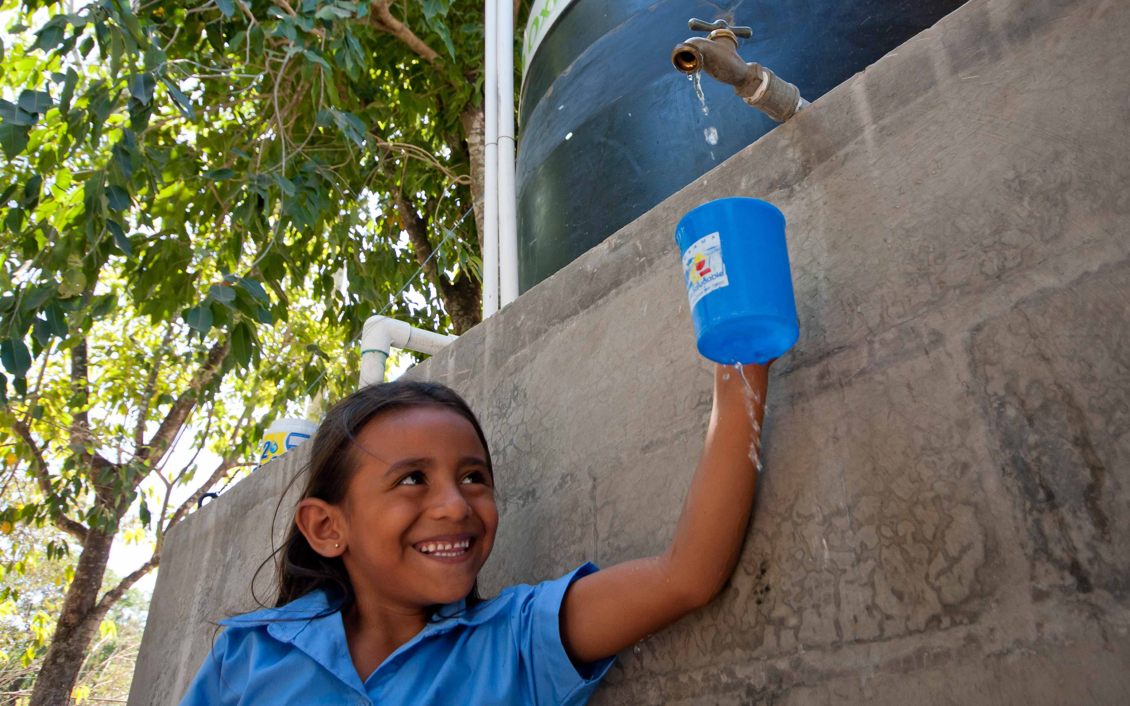 """A girl draws water from a community """"healthy well"""" in Zacatecoluca, El Salvador, built by Oxfam partner PRO-VIDA and designed to resist contamination from floodwater. """"Before we had the well, there was a lot of diarrhea; the number of cases has gone way down,"""" says  Estela Umaña, a resident of El Salitral."""