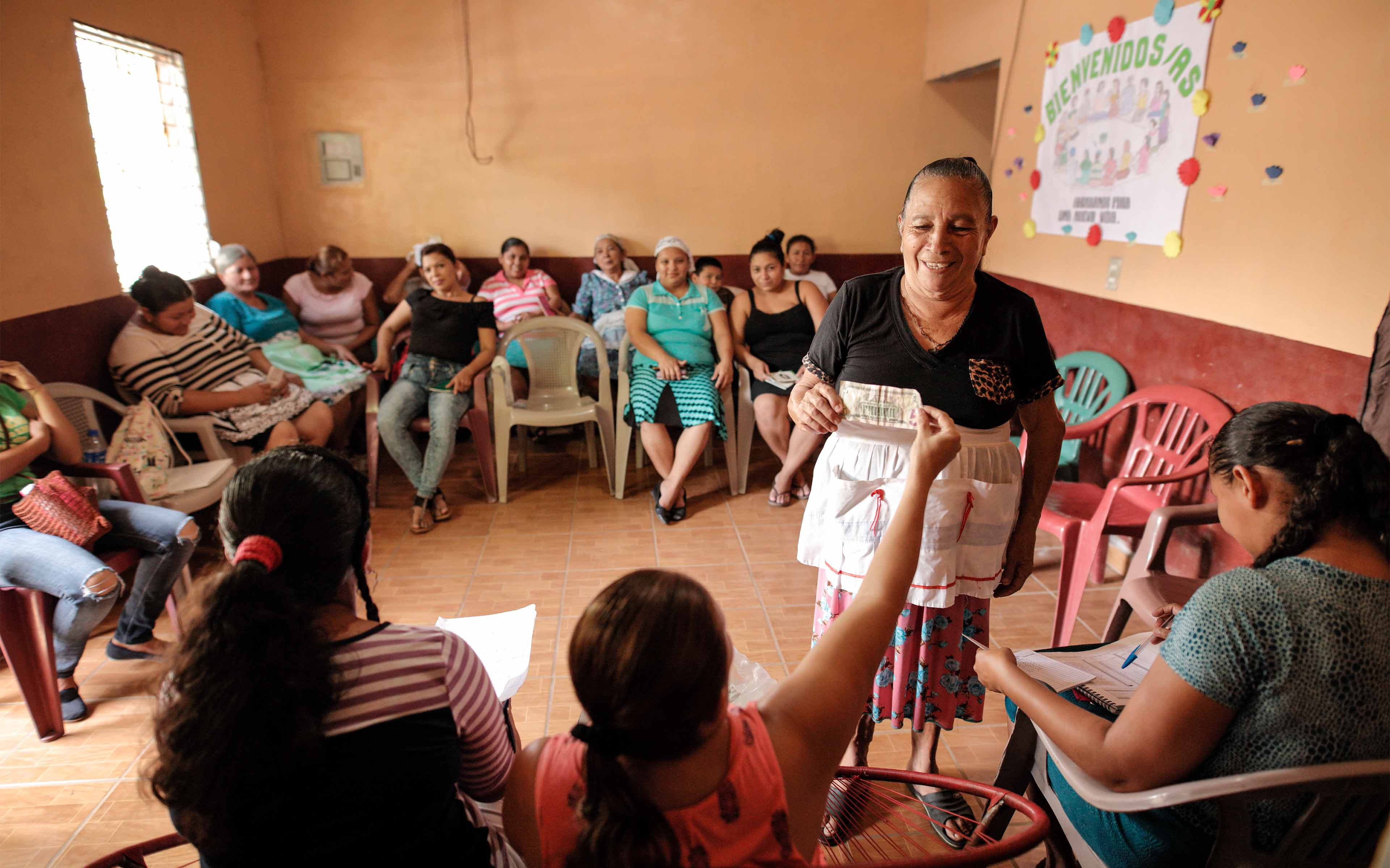 Maria Angela Guevara makes a savings deposit at a weekly meeting of her Saving for Change group in Calvario.
