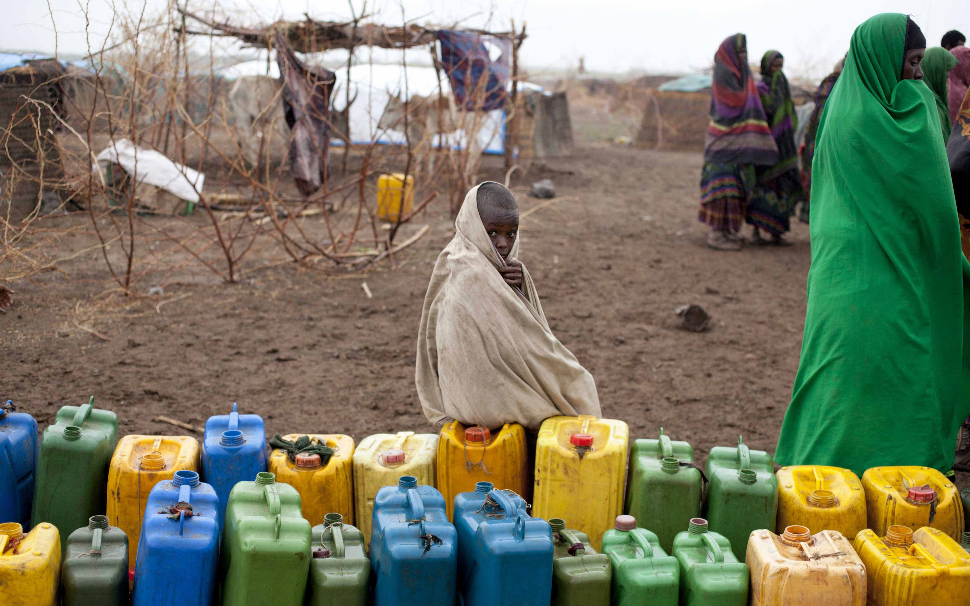 In the Siti Zone of Ethiopia's Somali region, a boy waits next to a collection of water jugs lined up to be filled with water trucked in by Oxfam and stored in a tank.