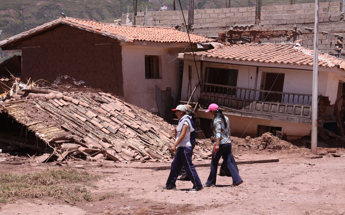 girls-walking-in-front-of-destroyed-houses.jpg
