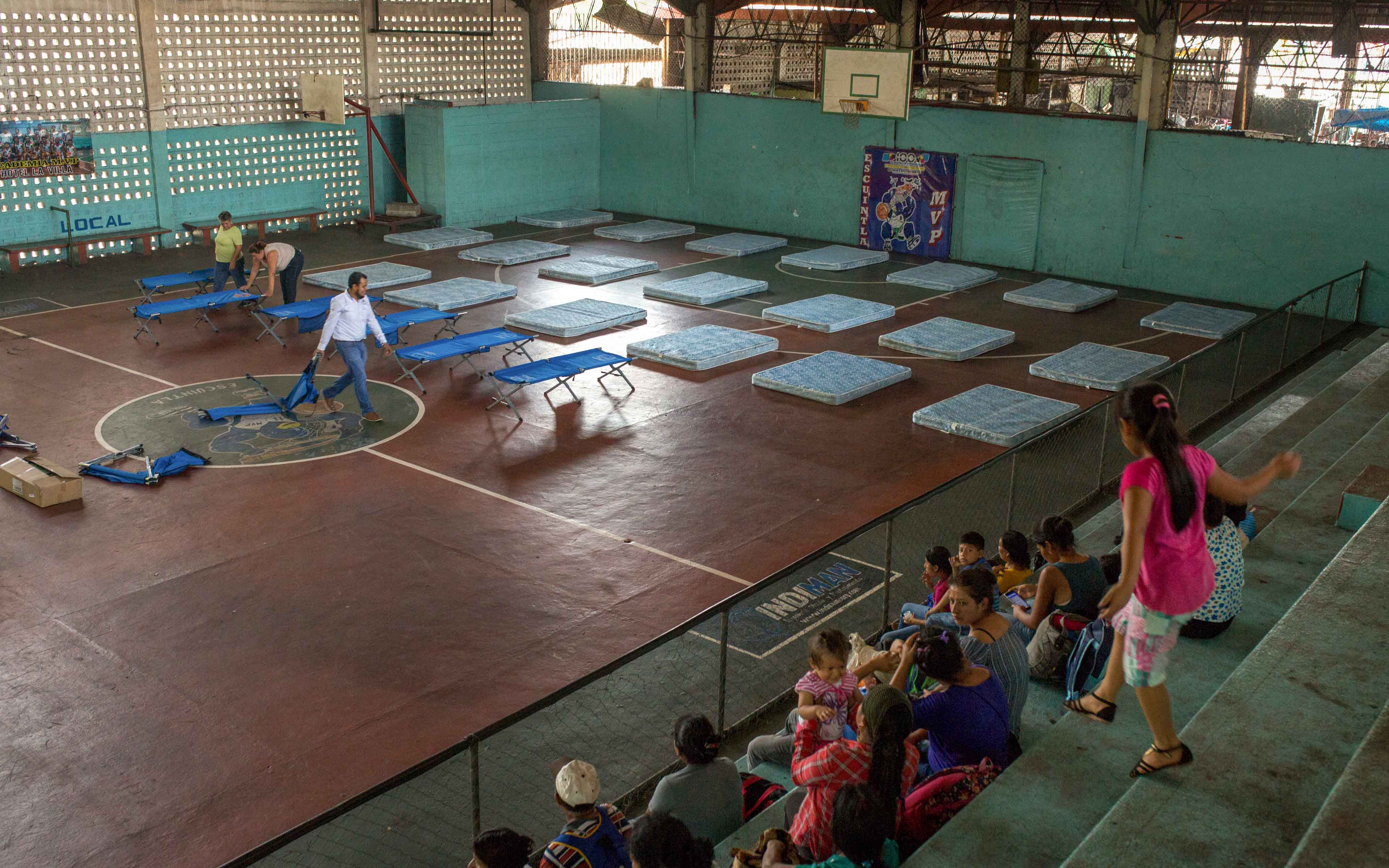 Families from La Trinidad wait to be assigned a place in the municipal gymnasium in Escuintla.