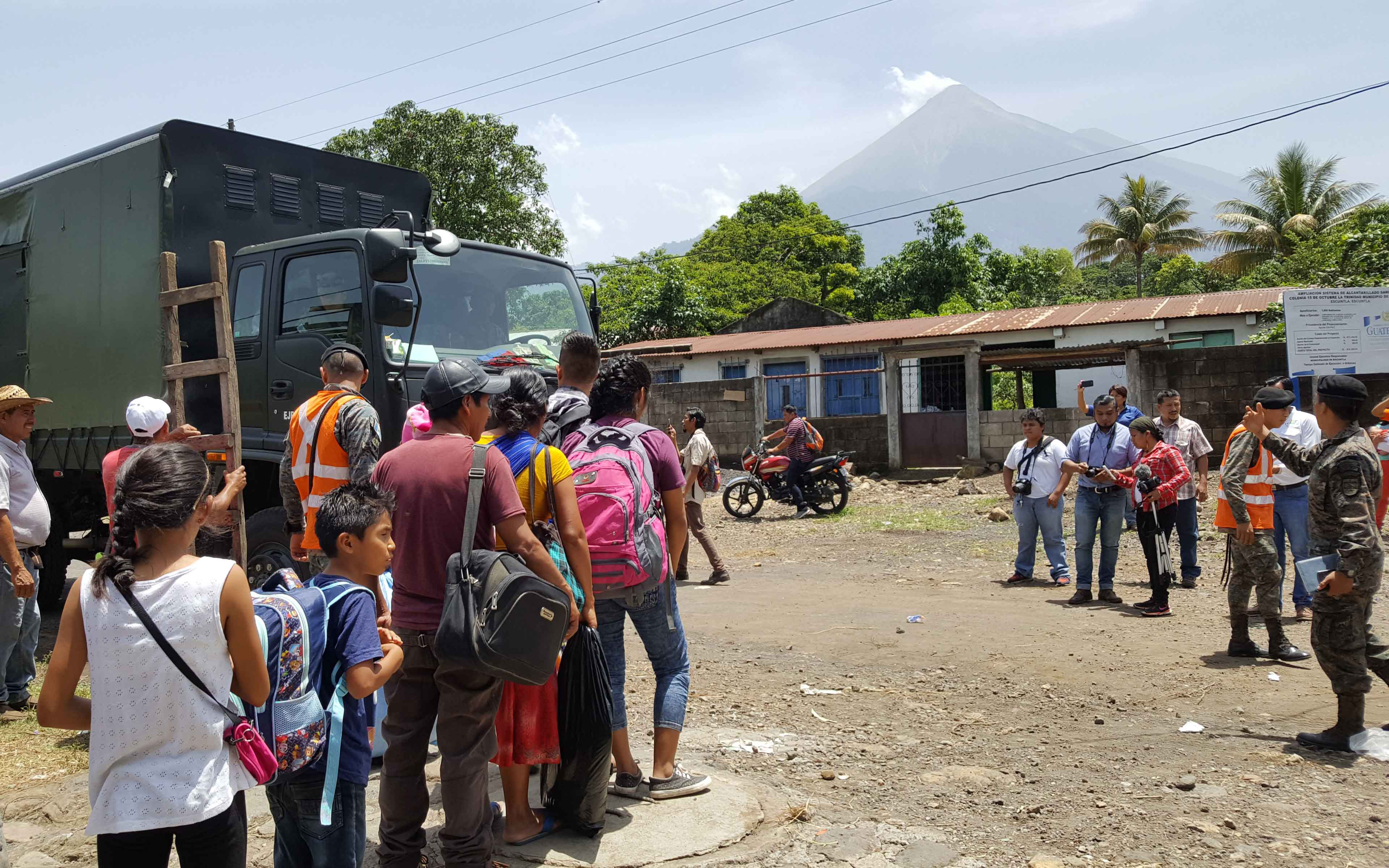 As steam blows out of the top of Fuego in the background, community members of La Trinidad prepare to board army trucks that will evacuate them to temporary shelter in the nearby city of Escuintla.