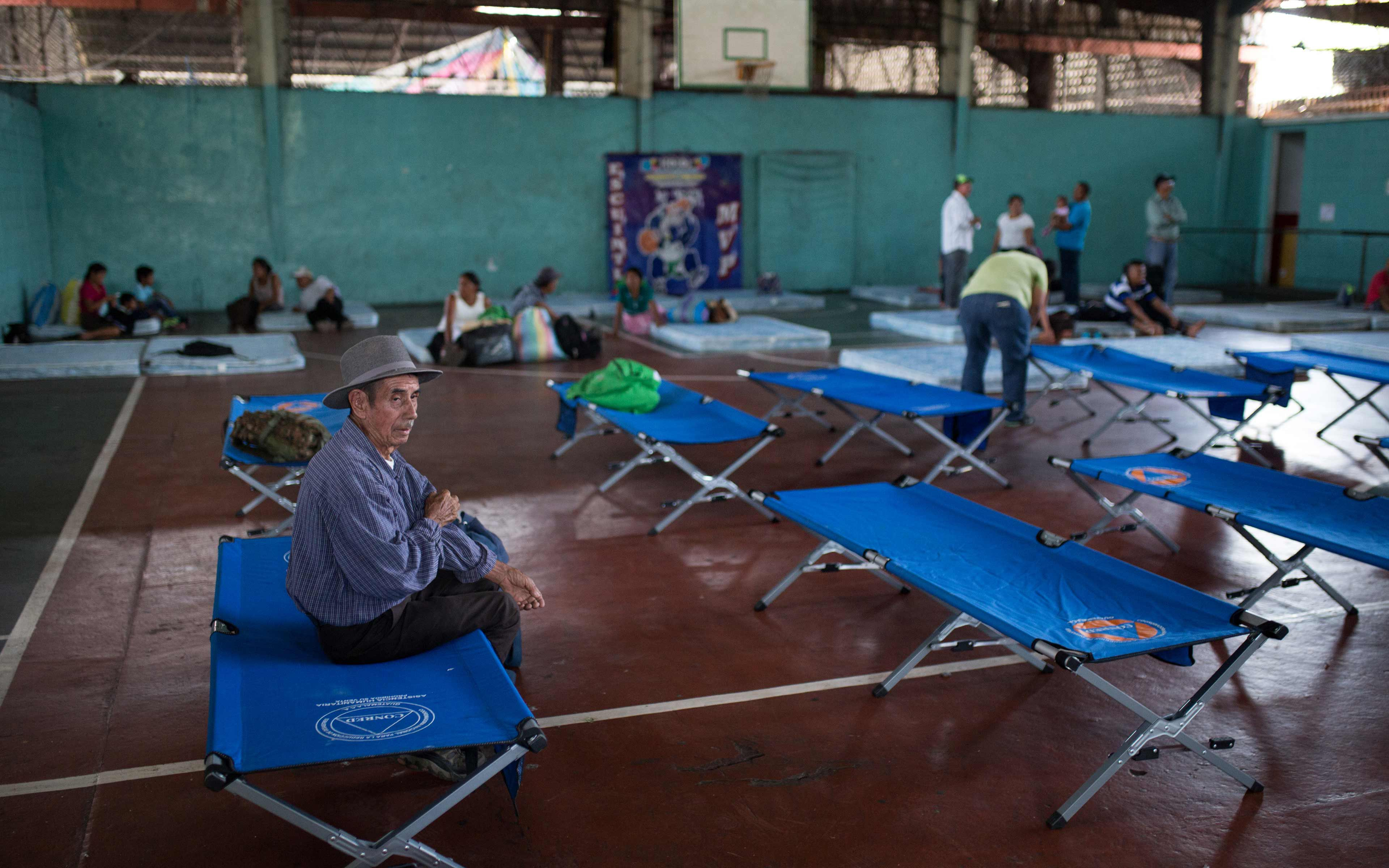 Gervasio López, 83, was assigned this cot in a temporary shelter at the gymnasium in Escuintla. He survived the war, nearly two decades as a refugee in Mexico, and then worked to build a new community in La Trinidad.