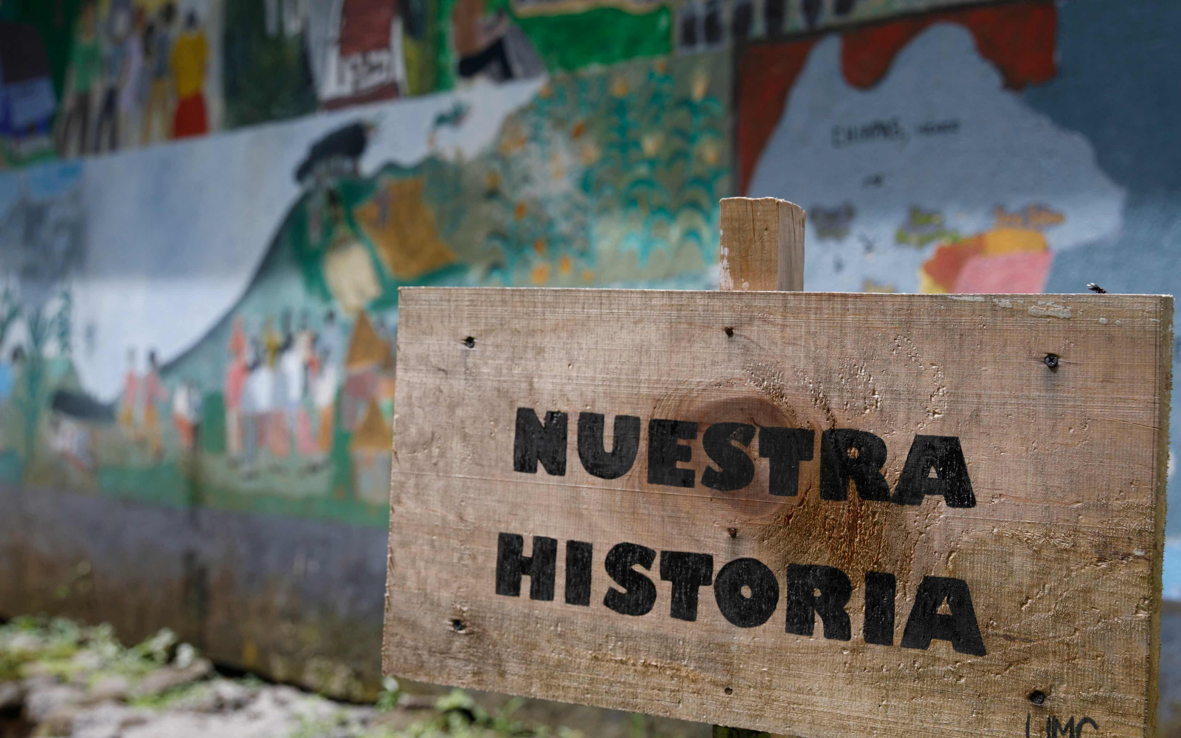 """""""Our Story:"""" A sign in front of mural depicting the tragic history of the community in La Trinidad, from a peaceful indigenous Maya village in the western highlands, to conflict and displacement to Mexico in the 1980s, and finally to repatriation and resettlement in Escuintla after the 1998 Peace Accords."""