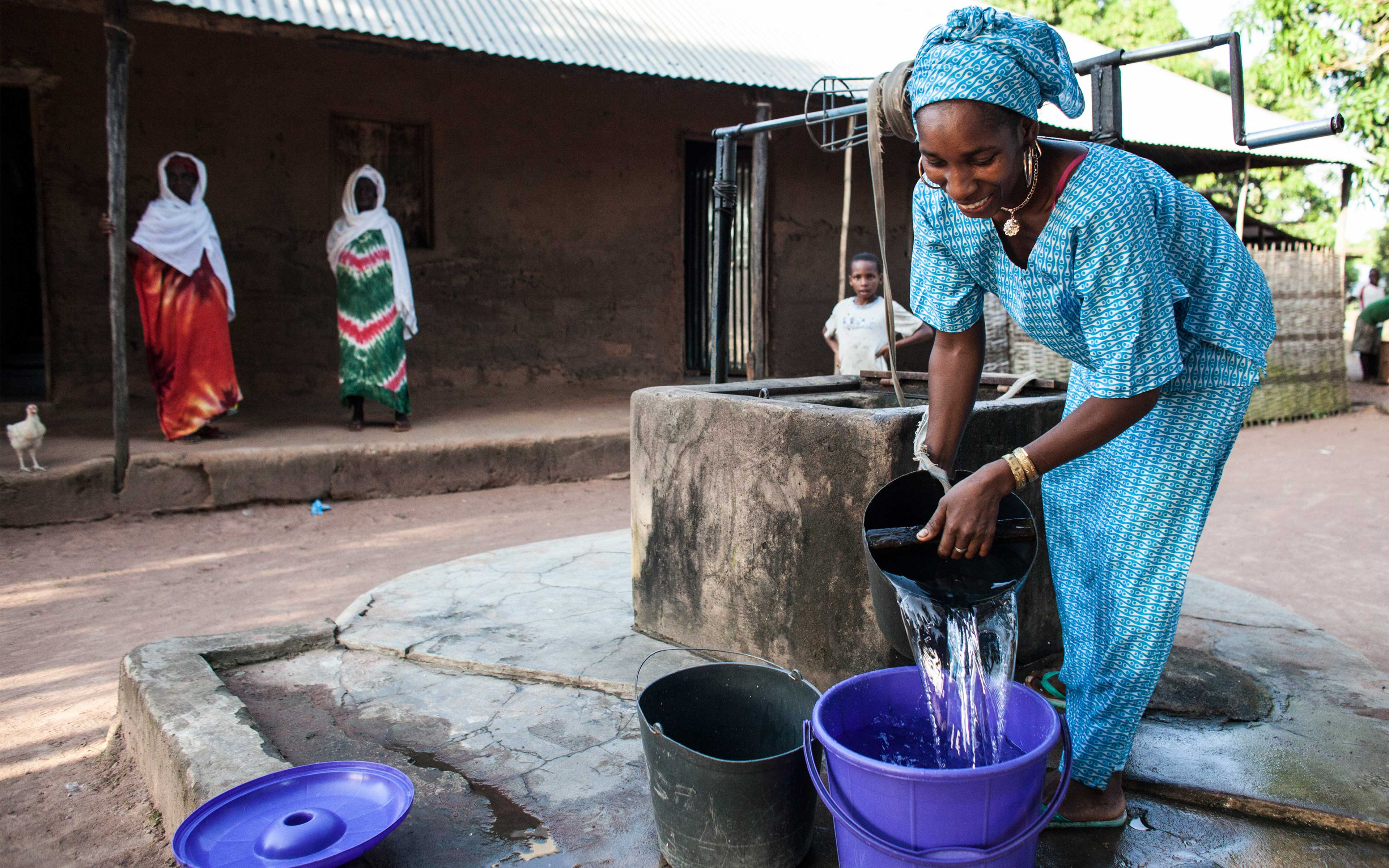 Ussai Balde gathers water at a well in Cuntabane, Guinea-Bissau—a town that borders Ebola-affected Guinea. During the epidemic, NADEL provided hygiene kits to community members here, as well as border surveillance and information about Ebola prevention.