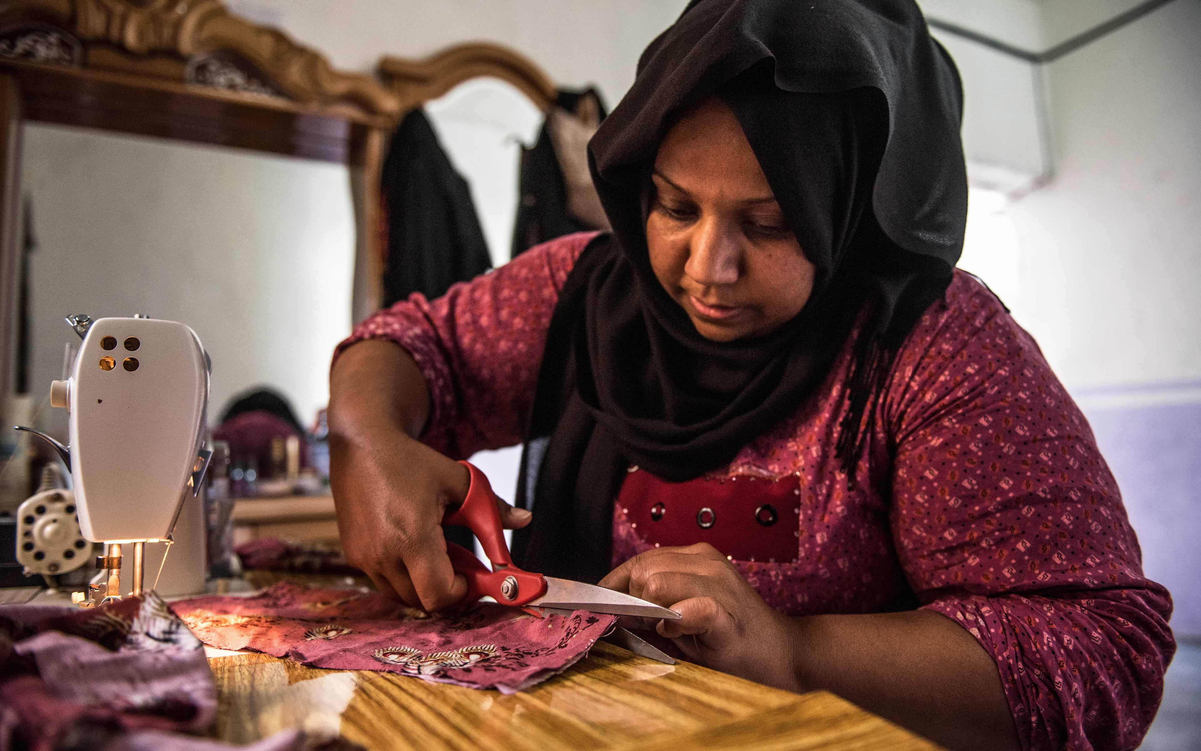 Zahia Hassan works at her sewing machine. After the occupation by ISIS ended, Hassan, whose name has been changed to protect her identity, returned to her community and, with Oxfam's help, has been striving to rebuild her business as a tailor for her village.