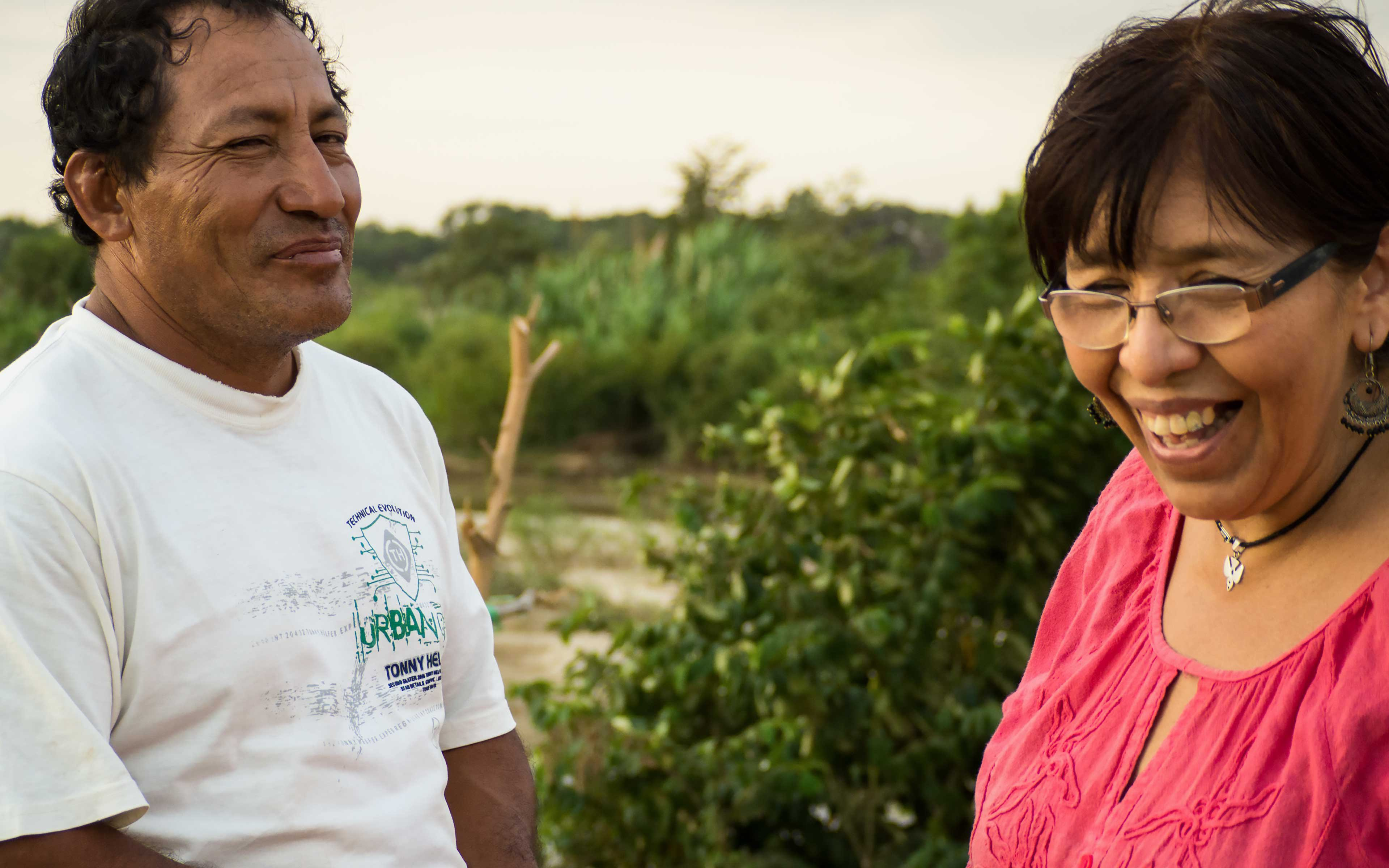 """Standing beside the La Leche river, Rosa Rivero (right) of CEPRODA MINGA shares a laugh with Andres Gonzales, the president of the Las Juntas community committee that focuses on disaster preparedness.  """"Now, we have a district committee that supports us,"""" says Gonzales. """"They're always here when the river is about to spill over. Ten years ago, they never would have come."""""""
