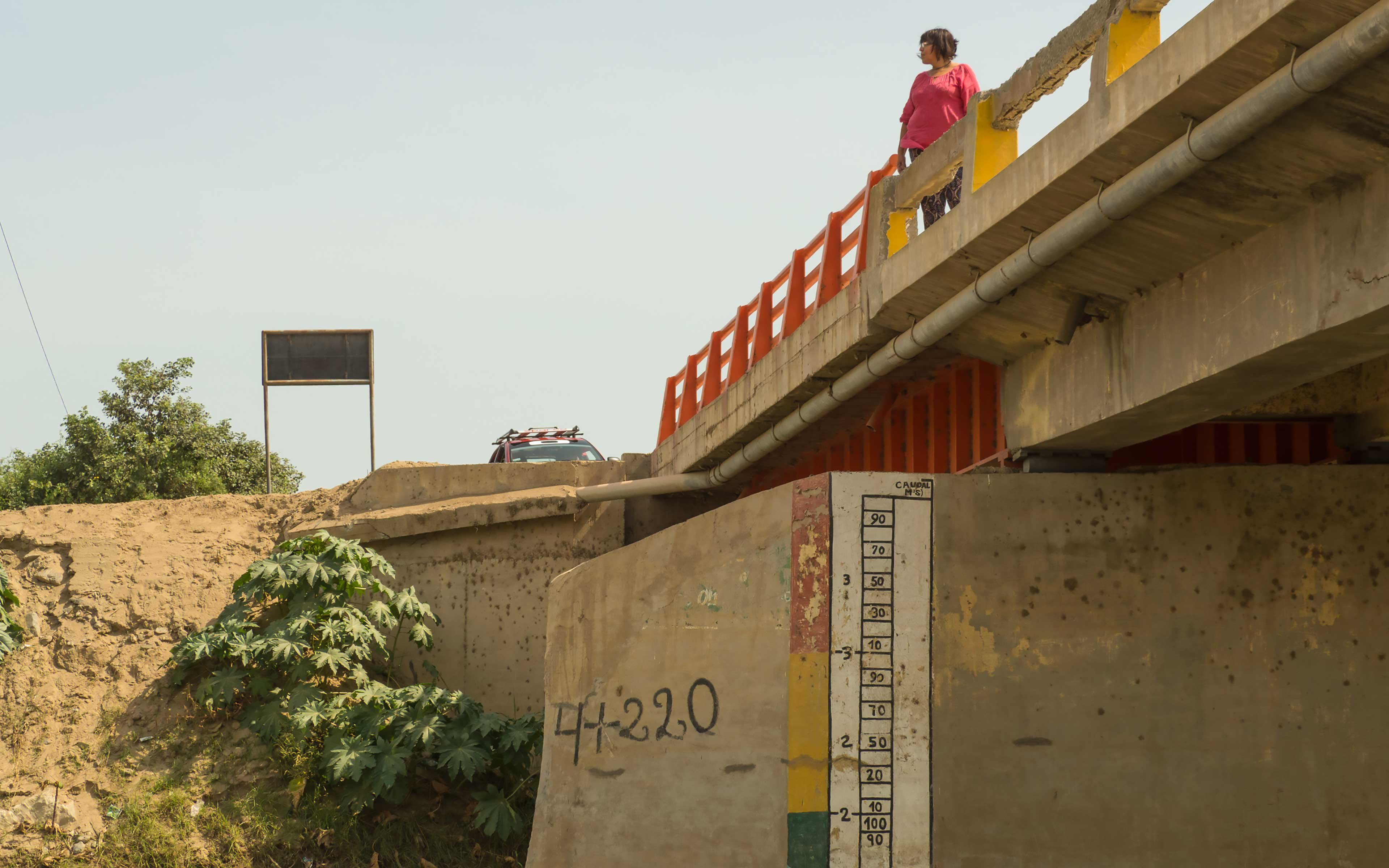Rosa Rivero stands on a bridge over the La Leche river. Measurements painted on the bridge are part of the Las Juntas flood early warning system.
