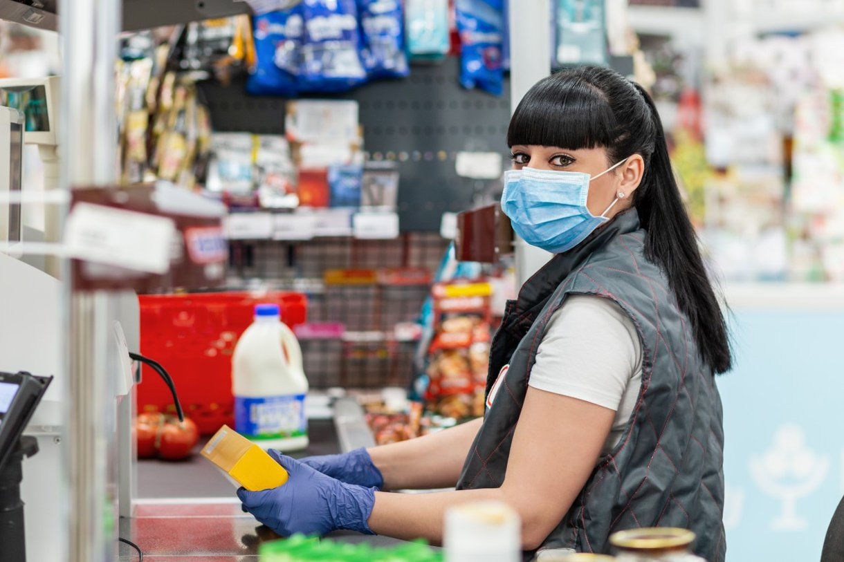 A store cashier wears protective gear as she rings up groceries. All states have work to do when it comes to protecting essential workers.