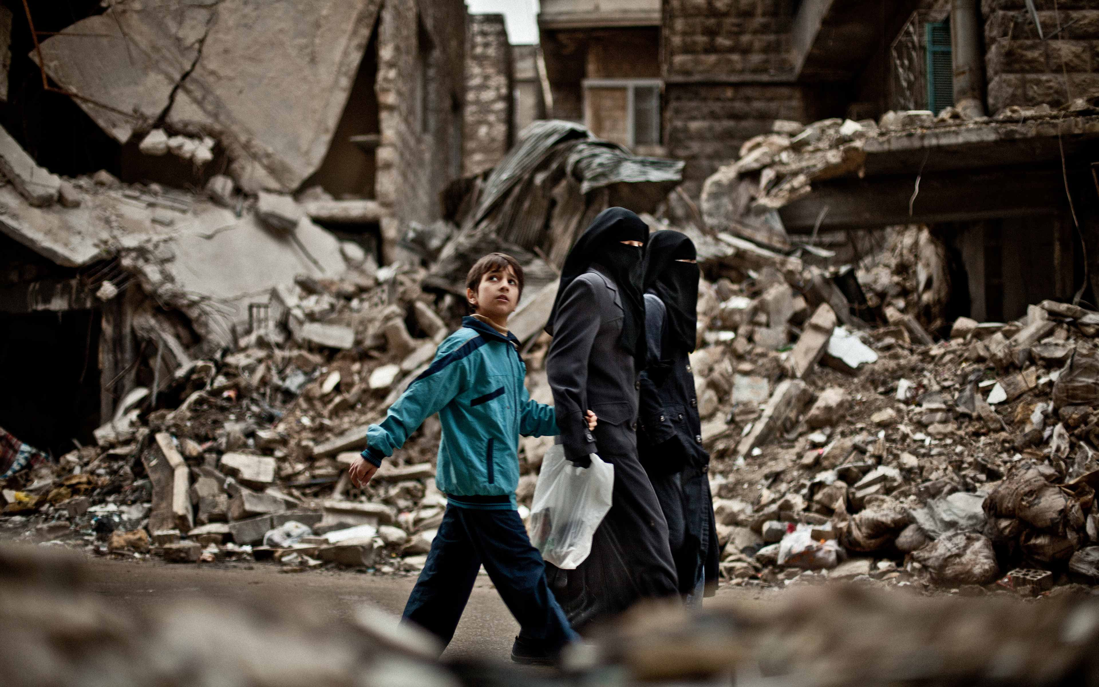 When Pablo Tosco, an independent photographer at the time, first saw this boy in Aleppo, Syria, in February 2013, he thought it was a sign of hope: a child looking skyward. Only later did he realize that the boy's glance upward was a cautionary one. The day was cloudy, and therefore somewhat safe for people to be out knowing that poor visibility meant the air raids would stop.