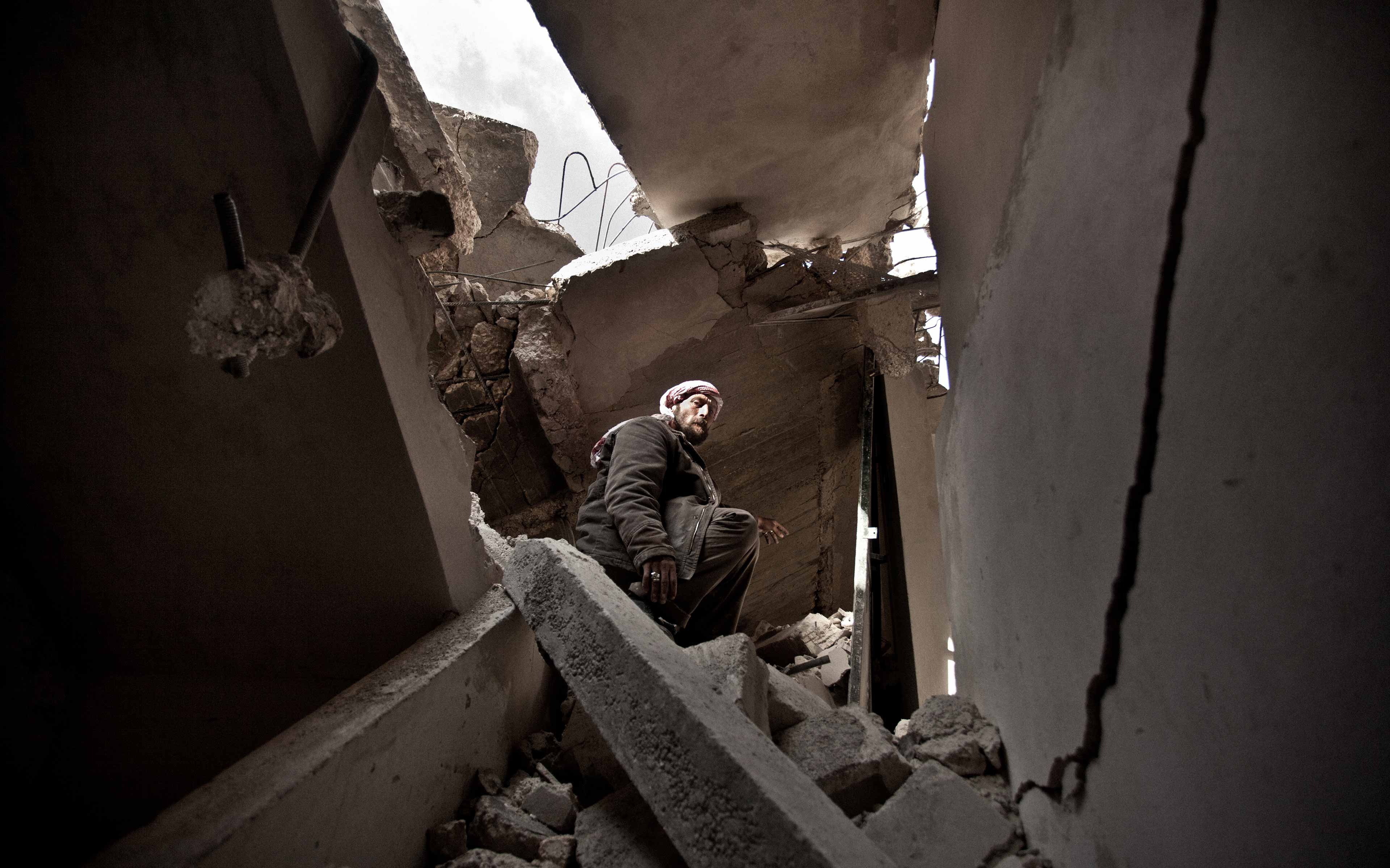 """Abu makes his way through the wreckage of his home in Aleppo in March 2013. The community was struck by a missile, leaving scores dead, including Abu's wife and two daughters. """"I think what moved me most was the solitude with which he was left,"""" says Pablo Tosco, who was an independent photographer at the time and helped Abu carry the bodies down the stairs."""