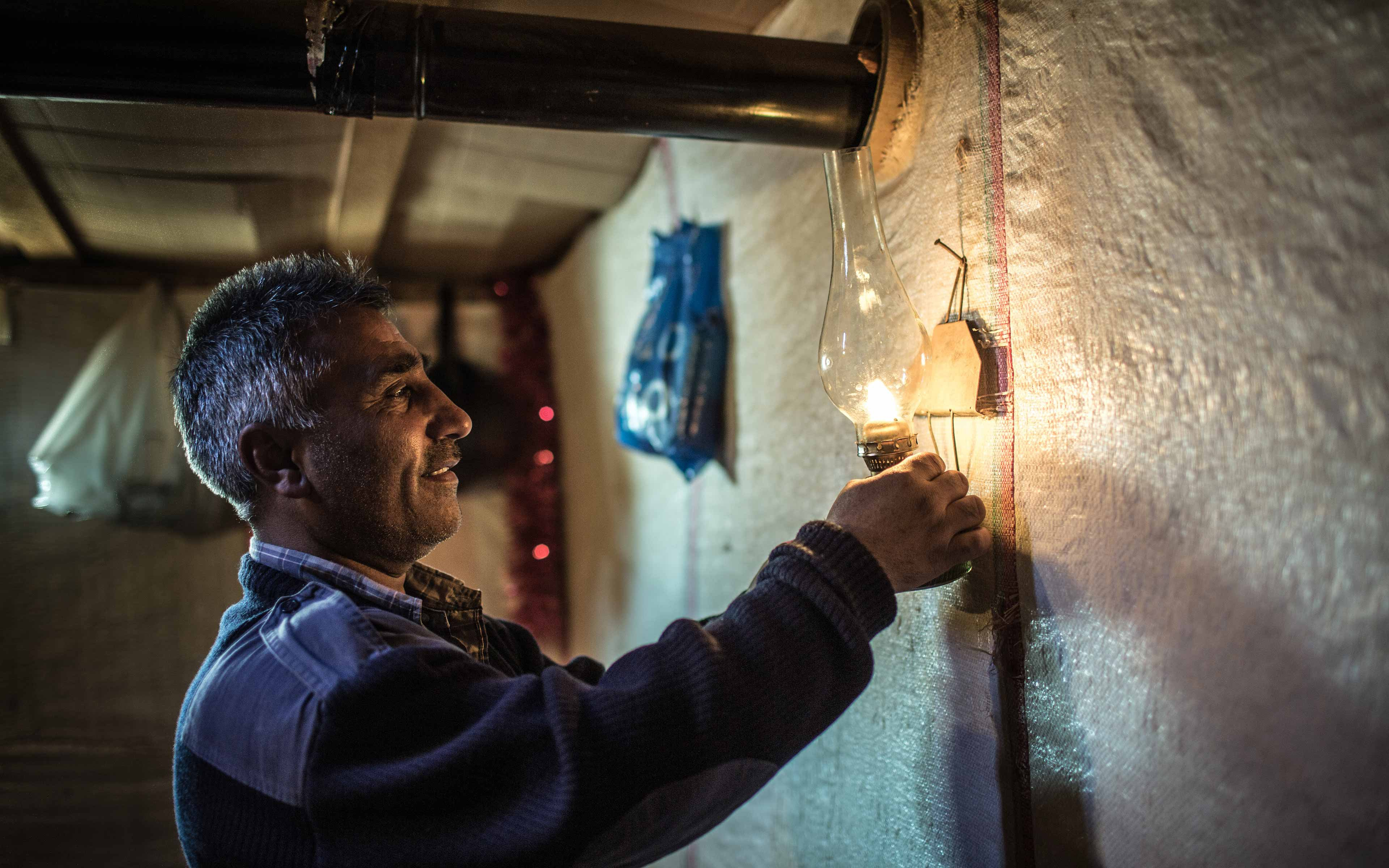 Abbas lights a kerosene lamp in a shelter made of plastic sheeting. He and his family fled from a suburb of Homs, Syria, and now live here in Lebanon. About 70 percent of Syrian refugees in Lebanon live below the national poverty line of $4 per person per day.