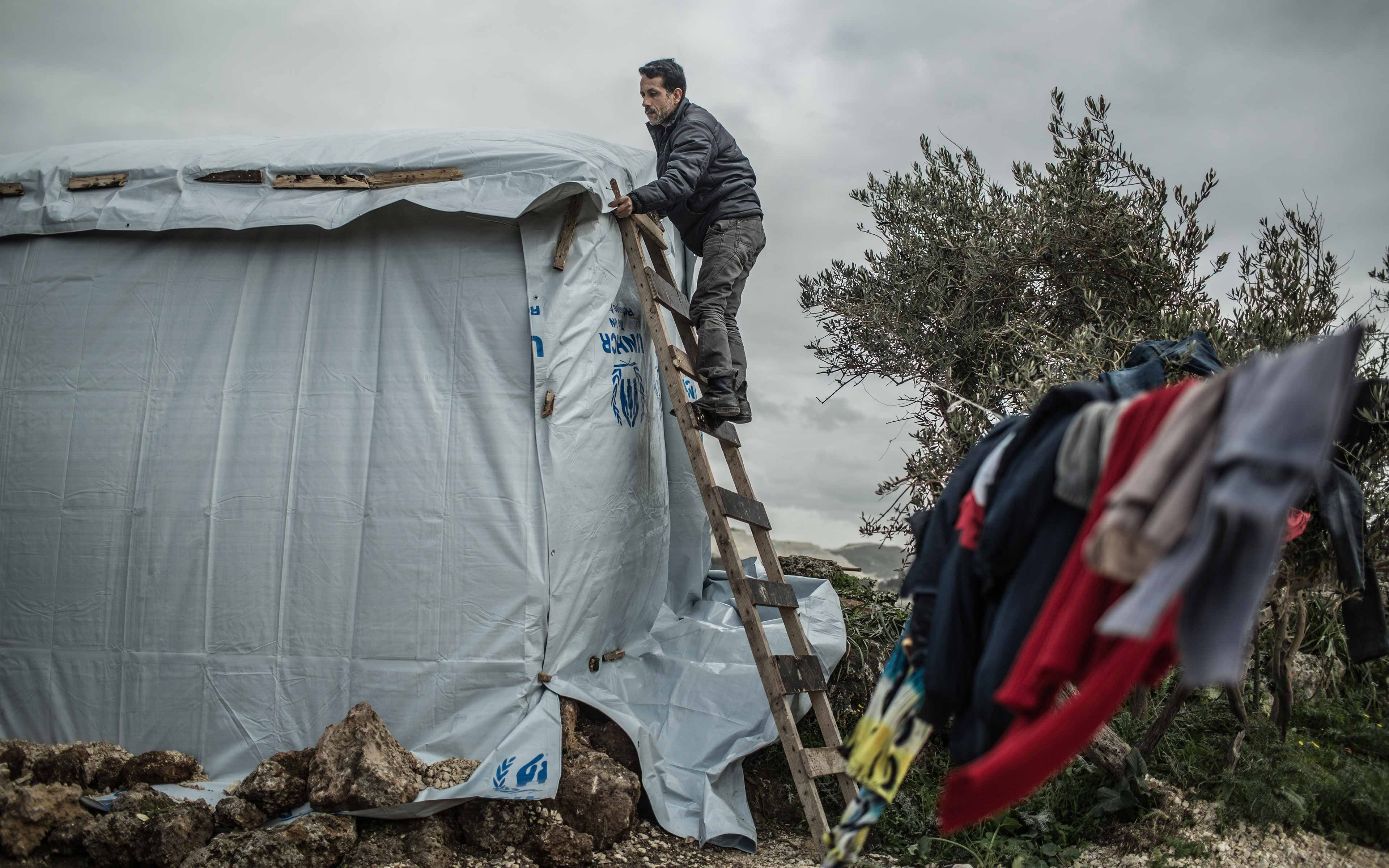 Ahmed works on a shelter made of wood and plastic sheeting in an informal settlement in northern Lebanon that is entirely dependent on humanitarian aid. He fled from Hasaka, Syria, with his family in 2012.