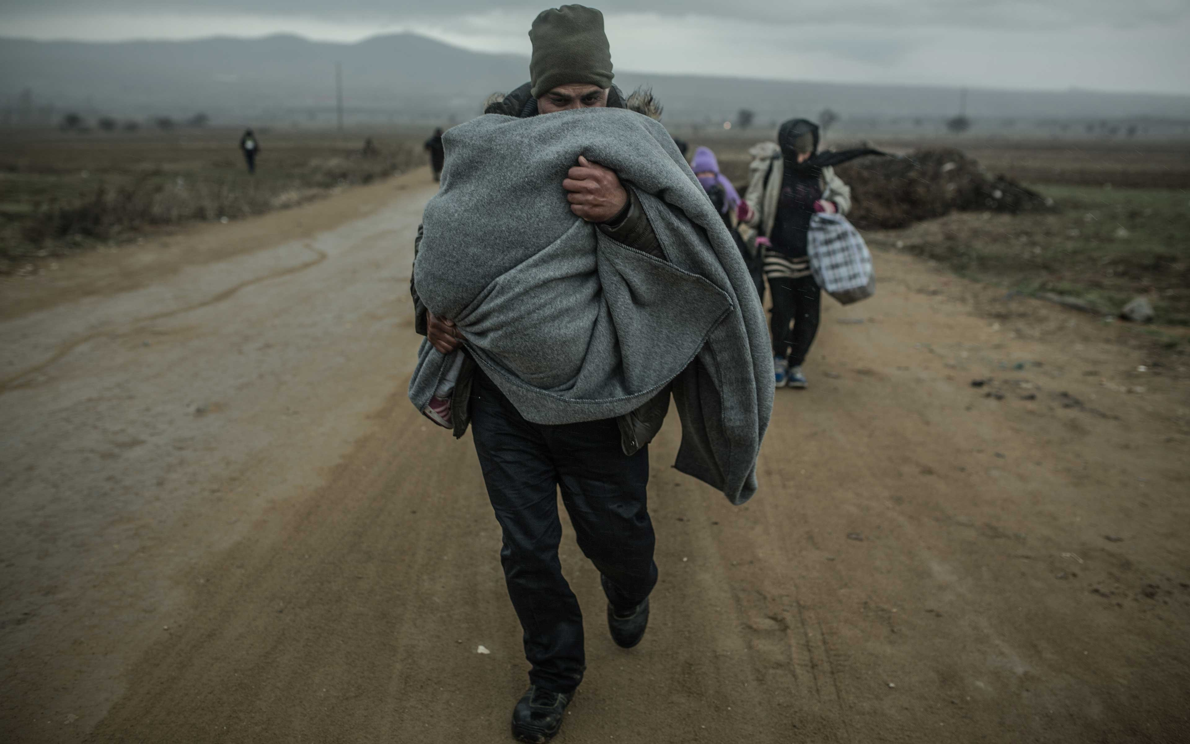 Khaled and his wife and children make their way through the cold and rain at Macedonia's border with Serbia in February 2016. At the time, thousands of people a day—from Syria and other war-torn places—were passing into Serbia, where they had 72 hours to cross the country.