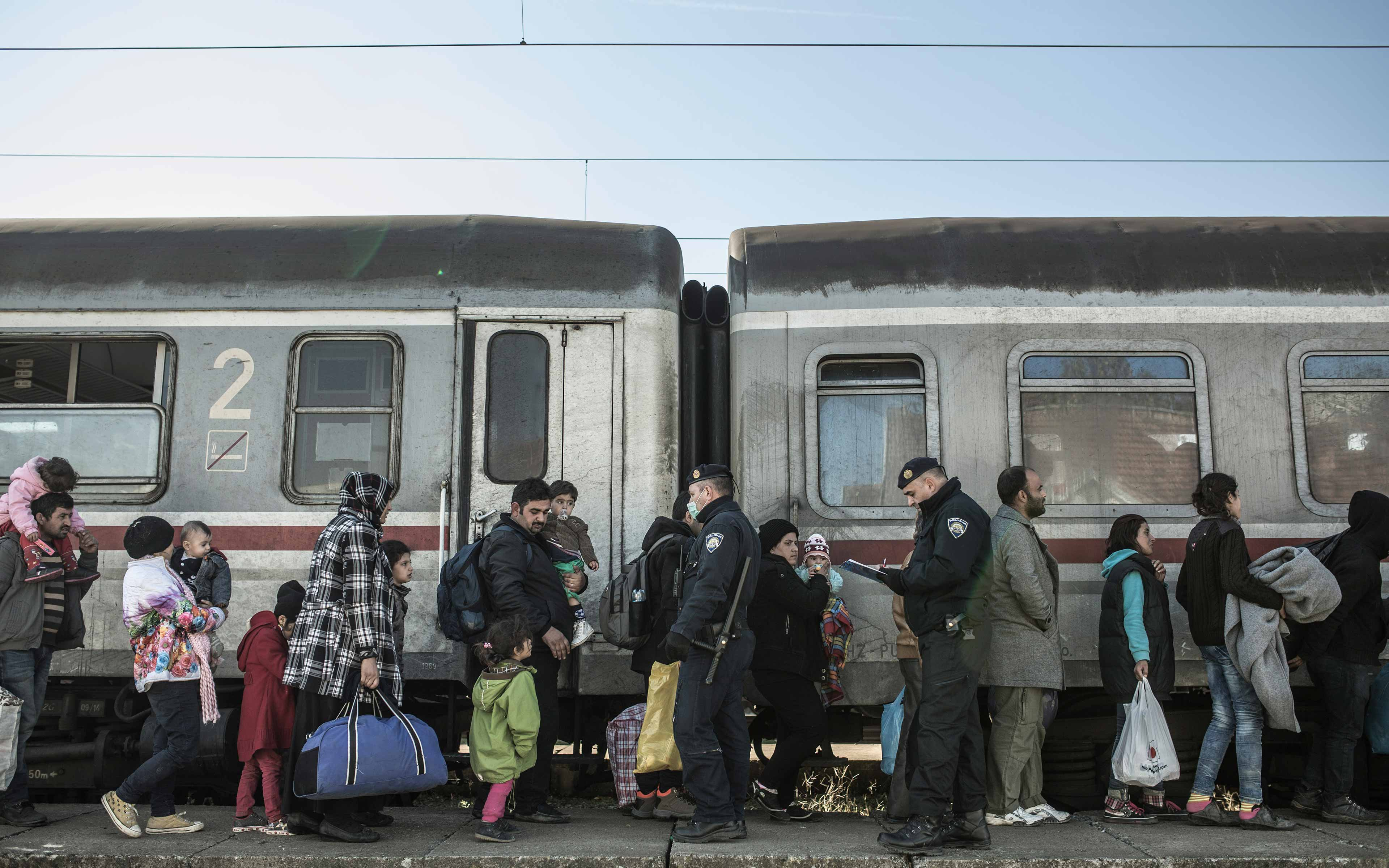 Refugees wait at a train station in Sid, Serbia.