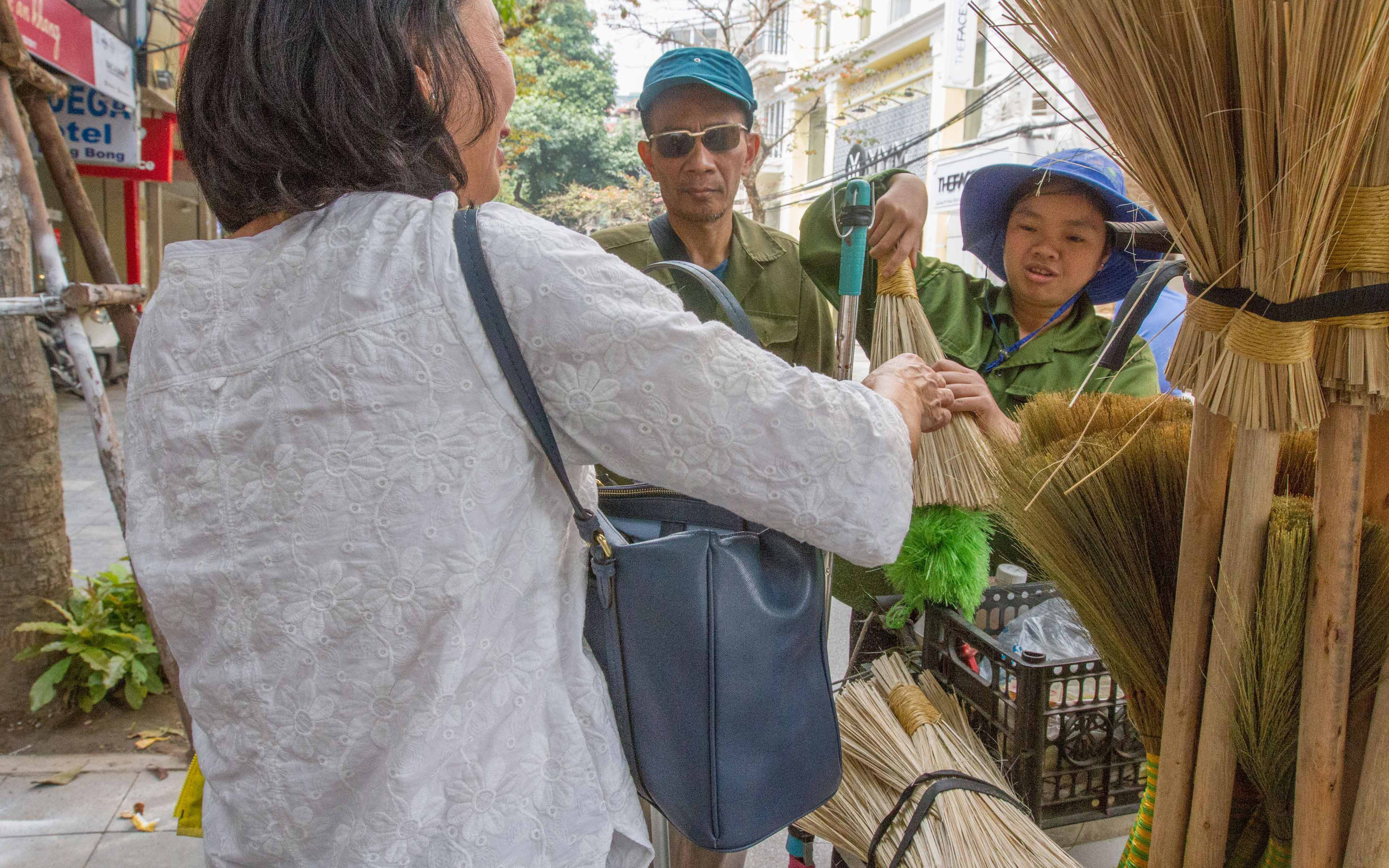 Phạm Thị Hậu and her uncle sell brooms to a customer on the streets of Hanoi. It was his idea for her to sell brooms and share the profit with the Blind Association in Hanoi's Hoan Kiem District.
